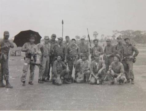 Congo rescue operators; Rip Robertson standing in back, 4th from left, with several Cuban exiles. The significance of the date - November 22, 1964 - and the open, black umbrella are curious.